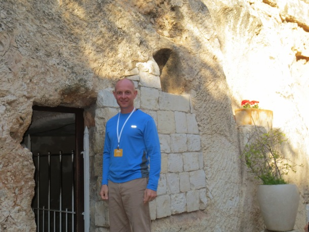 Standing by the door of supposed site of Jesus' tomb, from which an angel rolled the stone away upon his resurrection.